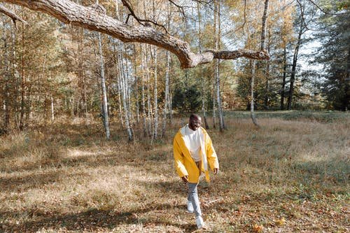 緑の芝生のフィールドを歩く黄色の長袖シャツと白いズボンの男