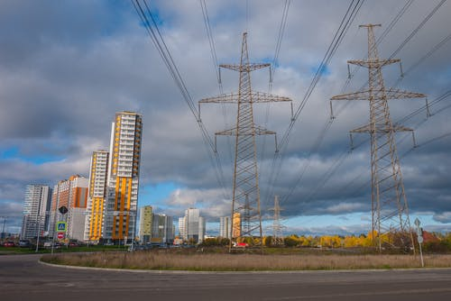 Electrical Posts And Power Lines Under Cloudy Sky