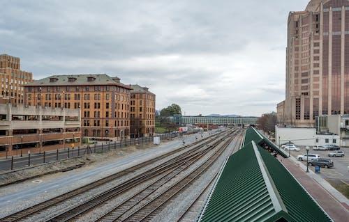 Brown and Green Concrete Building Near Train Rail