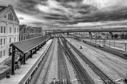 Grayscale Photo of Train Station Near The Highway