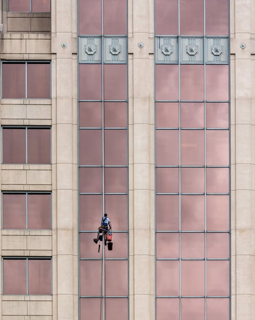Man Hanging From A Building Cleaning The Glass Windows
