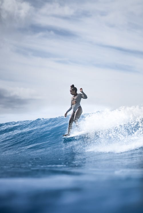 Full length fit female in white swimwear surfing board on foamy sea waves under clear blue skies on sunny weather
