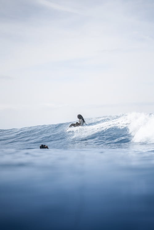 Faceless black woman fell from surfboard on sea surface