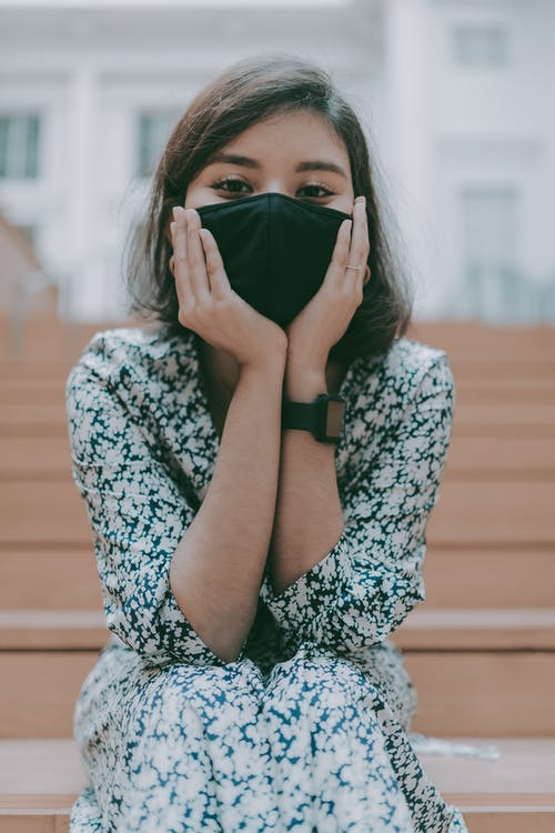 Young calm brunette in casual dress covering face with protective mask while sitting on wooden stairs on street and holding face in hands while looking at camera
