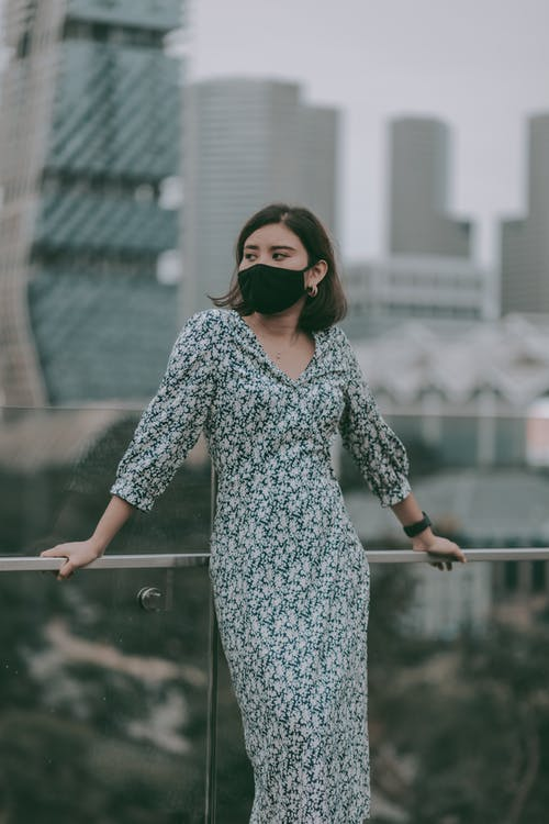 Stylish woman in mask standing near building glass railing
