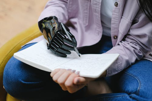 Woman with modern prosthesis of hand writing in notebook