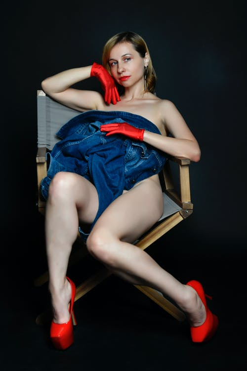 Full body of sexy young female model sitting on chair and covering naked body with denim jacket against black background