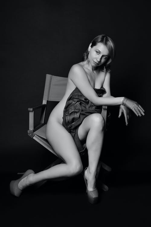 Full length of black and white sensual naked young female model in high heels and gloves sitting on chair ad covering body with cloth in dark studio