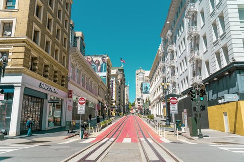 City street with tram rails and crosswalks with pedestrians