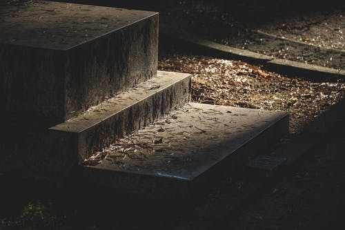 From above of aged tombstone placed on granite step in cemetery at night