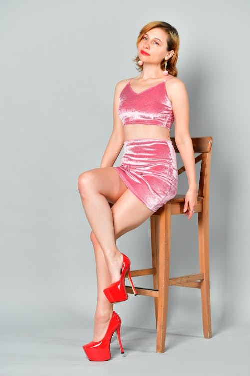 Alluring young woman in mini skirt and high heels sitting on stool in studio