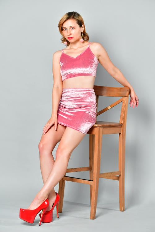 Full body of confident young female model with red lips in high heels and mini skirt and crop top leaning on wooden chair and looking at camera against white background