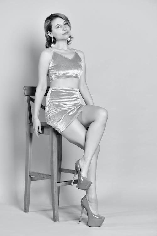 Stylish female sitting on wooden chair in light studio