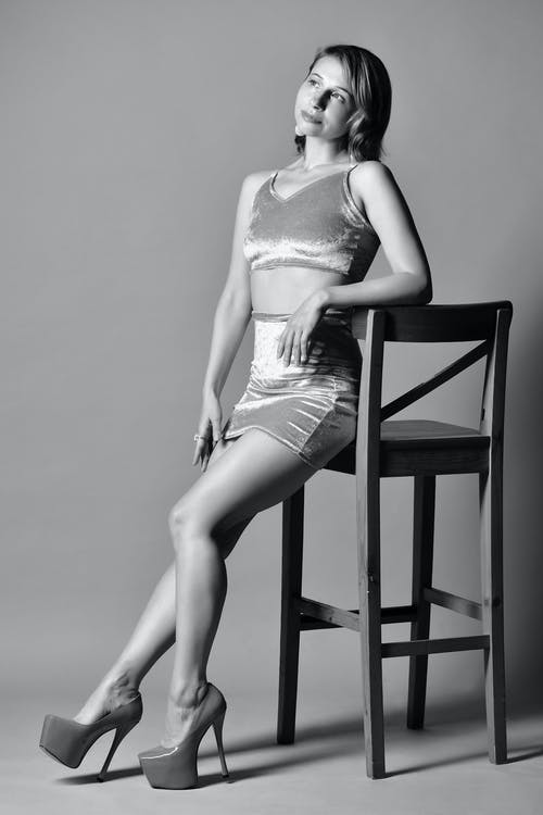 Black and white of positive female in sexy clothes and high heels leaning on wooden chair placed in studio