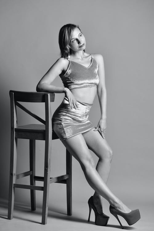 Black and white of sensual female in mini skirt and high heels leaning on wooden chair and looking away against light background in studio