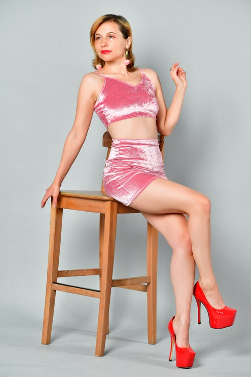 Charming female in sensual clothes and high heels sitting on chair