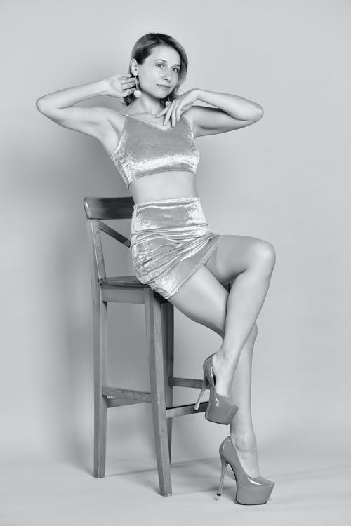 Black and white of seductive model in trendy outfit and high heels sitting with raised arms and crossed legs on chair in light studio