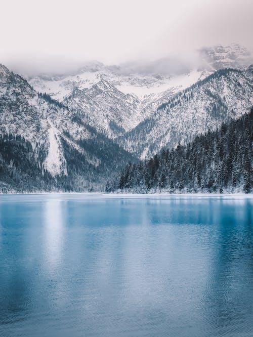 Lake Near Mountain Range Under White Sky