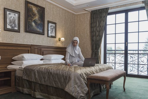 Woman in White Hijab Sitting on Bed Using Macbook