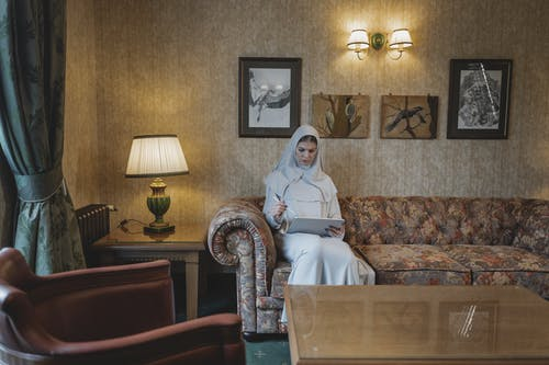 Woman in White Hijab Sitting on Brown and Beige Floral Sofa