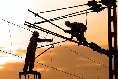 Silhouette of Two Electricians Working