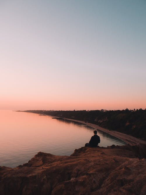 Man Sitting On A Cliff Near Body of Water
