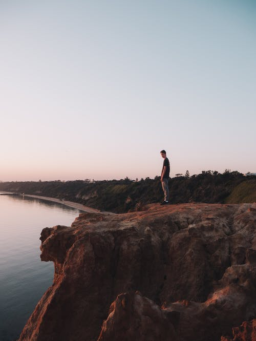 Man Standing on Brown Rock Formation Near Body of Water