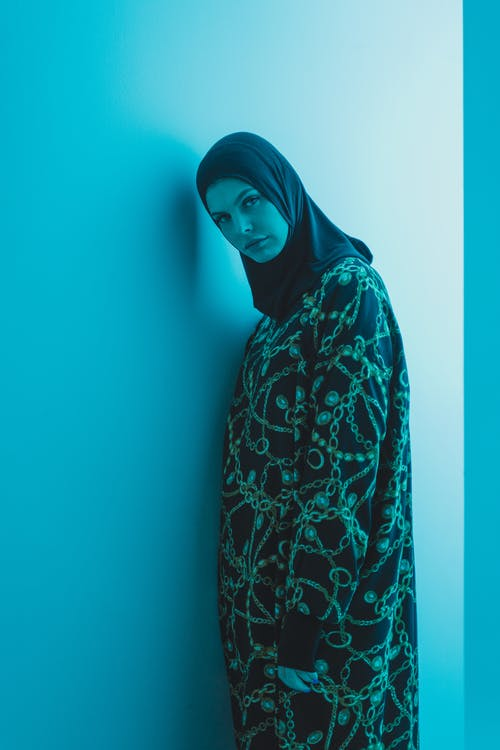 Woman in Black and White Hijab Standing Beside Green Wall