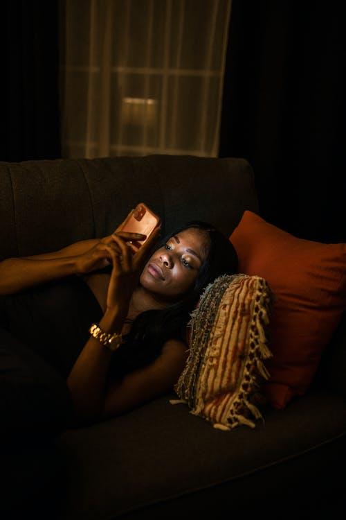 Femme En Débardeur Noir Allongé Sur Un Canapé Marron