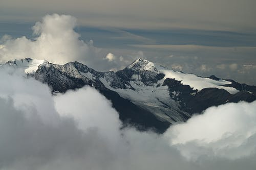 White clouds over snowy mountains