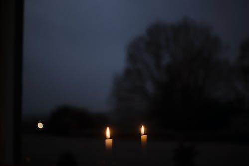 Burning candles on windowsill at night