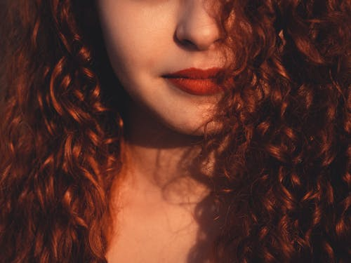 Unrecognizable beautiful female with dark reddish fluffy hair and vivid red lips in daylight