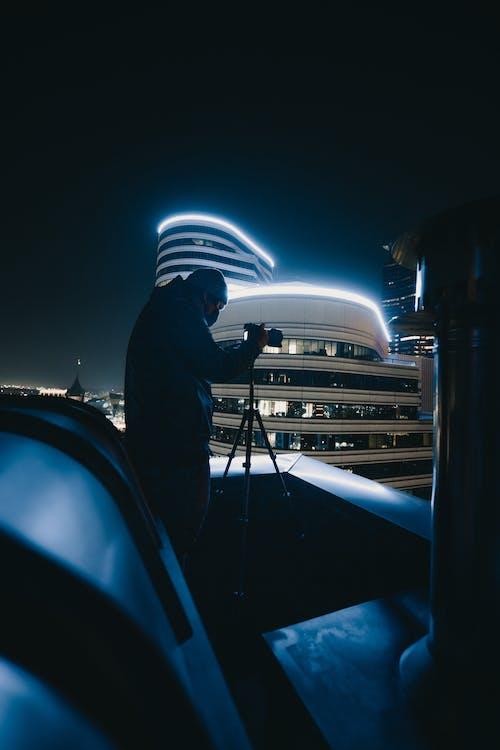 Man in Black Jacket Standing on Bridge during Night Time