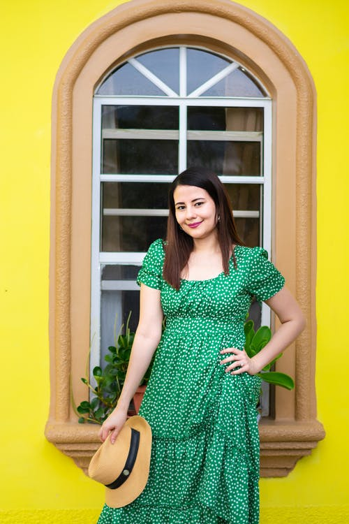 Woman in Green and White Polka Dot Dress Standing Beside White Wooden Window