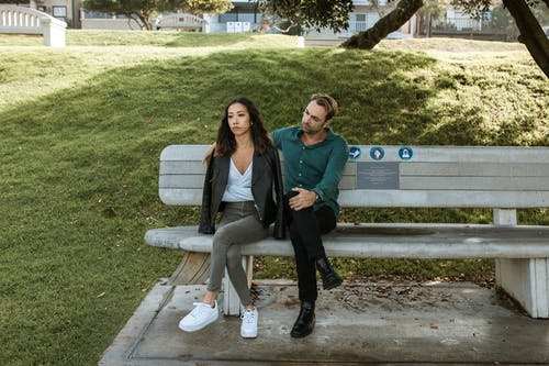 Man And Woman Sitting On A Bench Having A Discussion