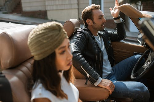 Man in Black Leather Jacket Sitting Beside Woman Having An Argument