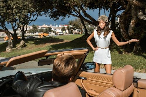 Wanita Dengan Gaun Tanpa Lengan Putih Duduk Di Kap Mobil