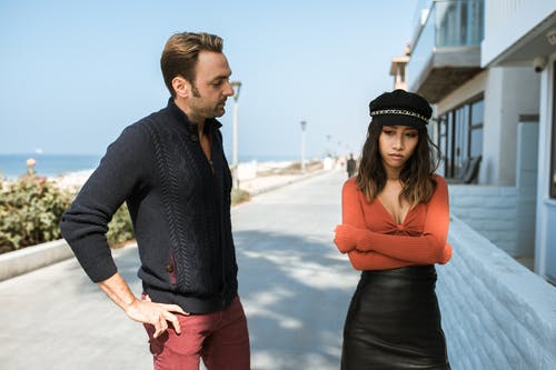 Man in Black Long Sleeve Shirt and Woman in Orange Long Sleeve Shirt Having An Argument