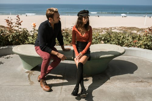 Man and Woman Sitting on Concrete Bench Near Sea Having An Argument