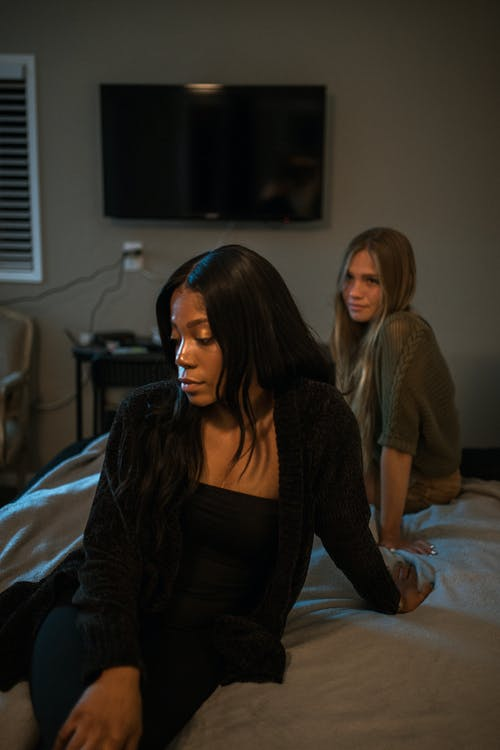 Two Women Sitting On Bed Having A Conversation