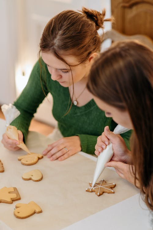 Two Girls Putting Icing On Cookies