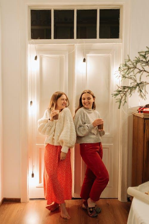 2 Woman Standing Beside White Wooden Door
