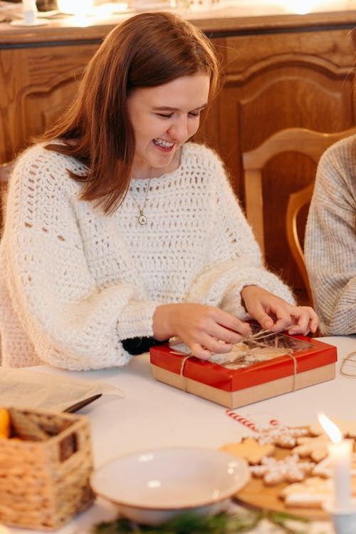 Woman in White Knit Sweater Sitting at the Table