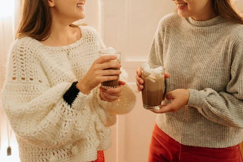 Woman in White Knit Sweater Holding Clear Drinking Glass