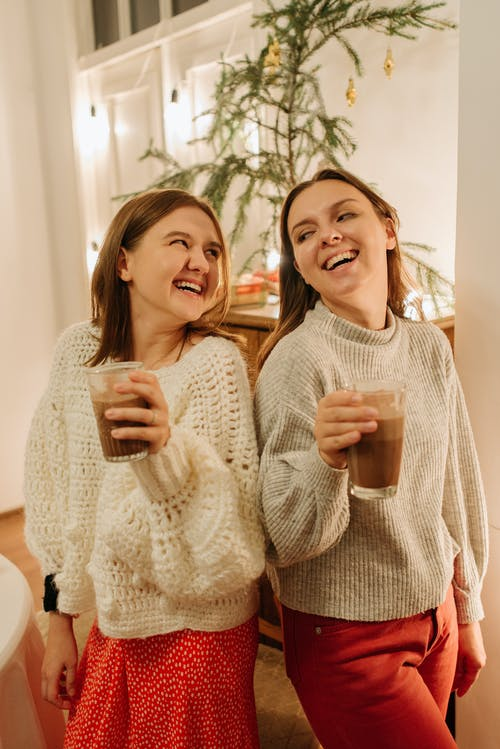 2 Women Smiling While Holding Drinking Glasses
