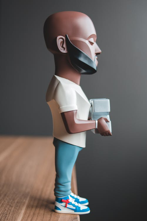 Figurine of modeler with logo on wooden table against gray wall at home