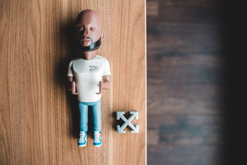 From above of miniature of fashion designer near logotype of brand on wooden table
