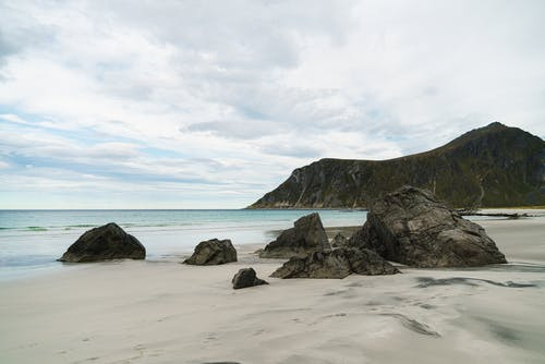 Remote empty coast with huge boulders and green mountain ridge on background in clouds