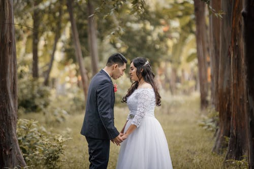 Elegant Asian couple holding hands on wedding day in park