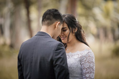 Anonymous man in suit near cheerful ethnic beloved in wedding dress with makeup in park